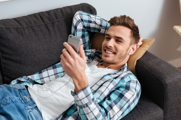 Image of young happy man dressed in shirt in a cage print lies on sofa in home and chatting while listening music
