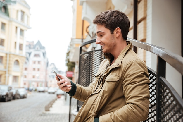 Image of young happy man walking on the street and chatting by his phone outdoors. look at phone.