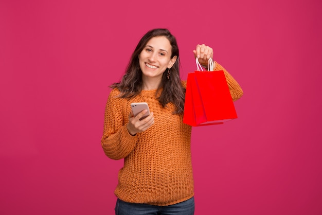 Image of young happy woman holding smartphone and shopping bags, online shopping