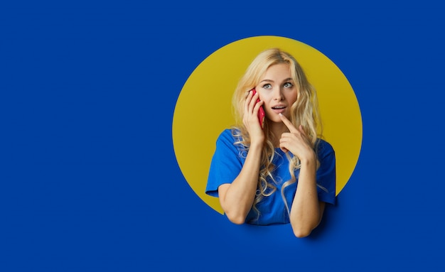 Image of young happy woman standing over a blue wall. woman peep out of a hole in the wall. looking to the side to take a selfie on the mobile phone.
