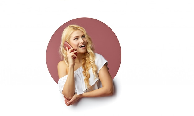 Image of young happy woman standing over white wall. woman peep out of a hole in the wall. looking to the side to take a selfie on the mobile phone.