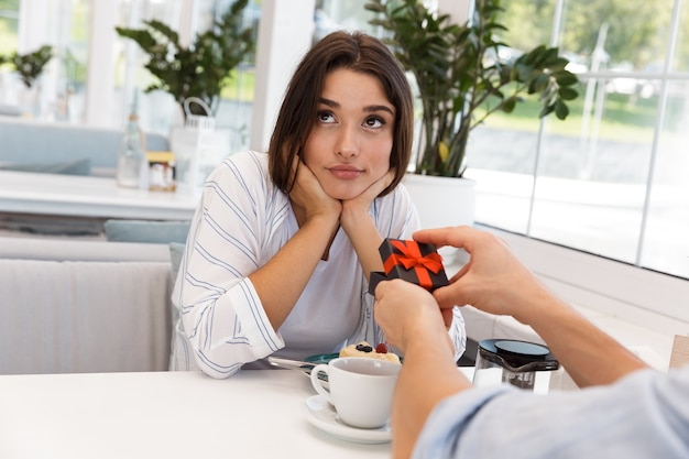 Image of young loving couple sitting in cafe. man gives a present to his sad girlfriend.