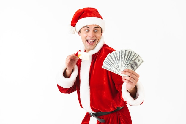 Image of young man 30s in santa claus costume holding dollar bills and credit card