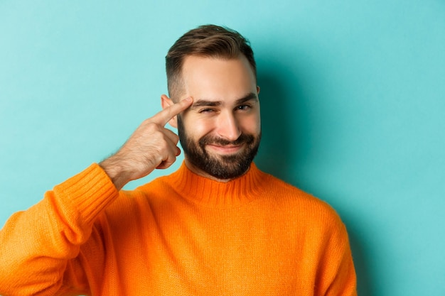 Image of young man in orange sweater, smiling and pointing at head, having an idea, praising good thought, standing over light blue background.