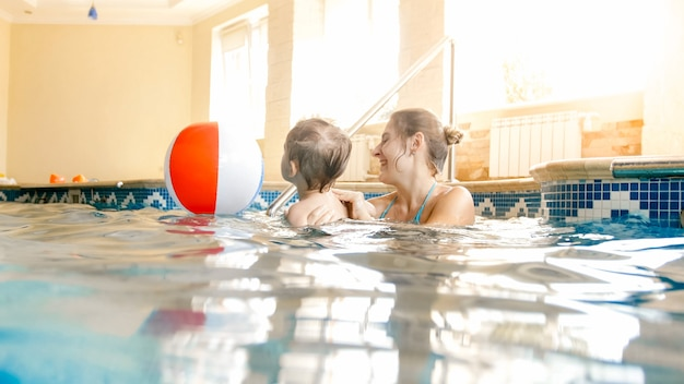 Image of young mother teaching swimming her little 3 years old boy child and playing with colorful beach ball at indoor swimming pool