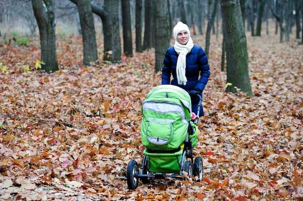 Image of young mother with baby trolley walking in autumn park.
