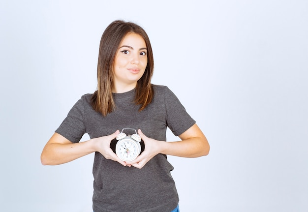 Immagine di un modello di giovane donna piacevole che mostra una sveglia.