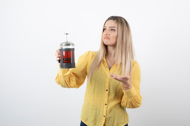 Image of a young pretty woman model holding a teapot .