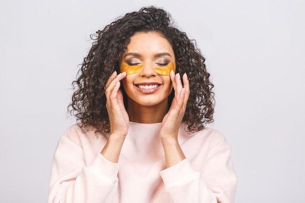 Image of young pure beautiful afro american woman standing naked isolated against white take care of her skin with under eye patches.