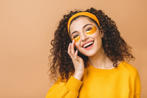 Image of young pure beautiful curly woman isolated over beige background take care of her skin with under eye patches.