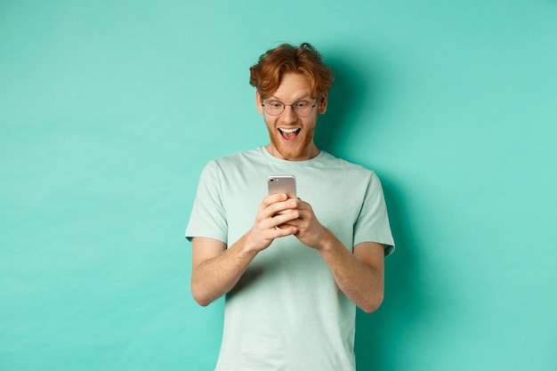 Image of young redhead man in glasses reading phone screen with surprised face, receive amazing promo offer, standing over turquoise background.