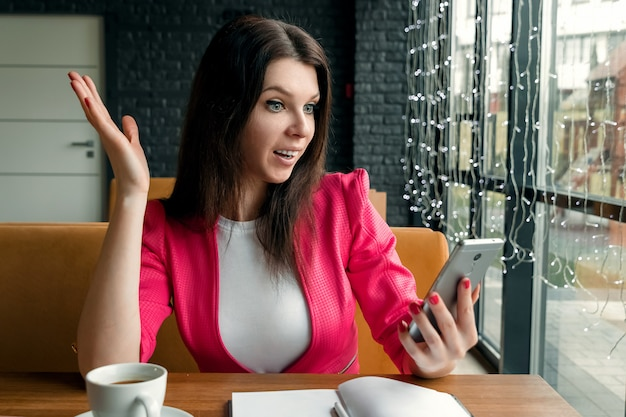 Image of young shocked excited business woman sitting indoors using mobile phone