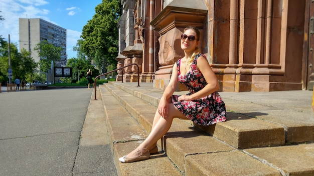Image of young smiling woman wearing sunglasses relaxing on old stone stairs on street