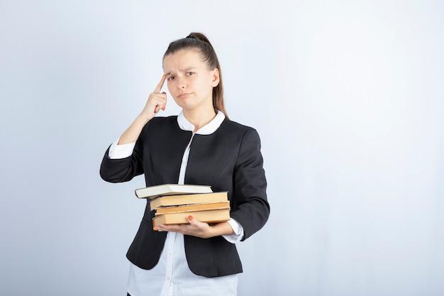Immagine di giovane studente con un mucchio di libri pensando su bianco.