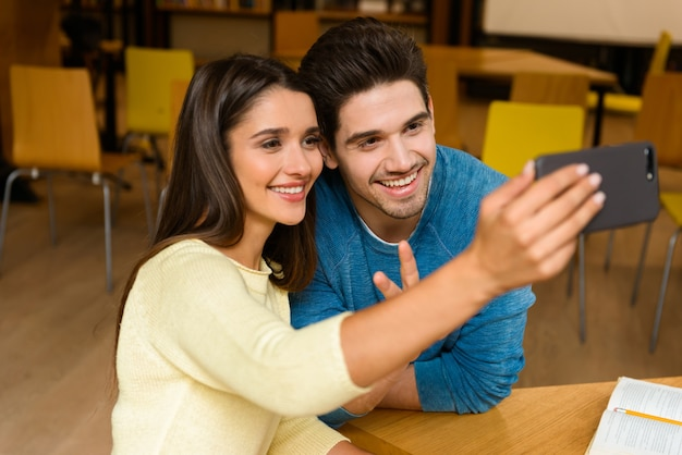 Image of a young students friends couple in library doing homework studying take a selfie by mobile phone.