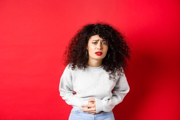 Image of young woman having stomach ache, bending from pain and complaining on painful menstrual cramps, standing on red background.