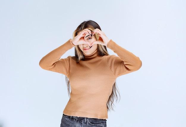 Immagine di un modello di giovane donna in maglione marrone che fa la forma del simbolo del cuore con le mani.