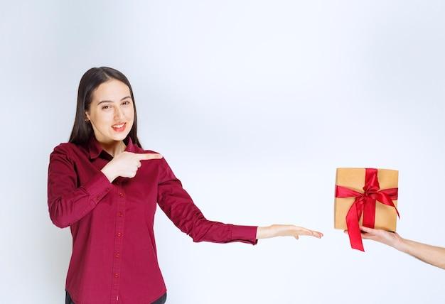 Immagine di un modello di giovane donna che punta a un regalo con fiocco sul muro bianco.