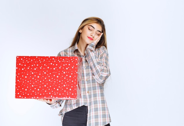 Image of a young woman model standing and holding a red gift box.