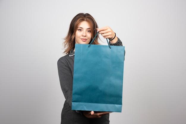 Immagine di una giovane donna che mostra in una borsa del negozio.