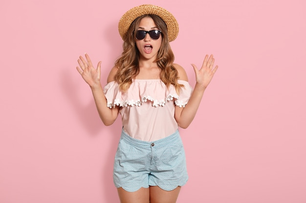 Image of young woman wearing pink blouse, blue short, sunglasses and summer straw hat standing with open mouth in shock, keeps hands up, has astonished facial expression. human emotions concept.
