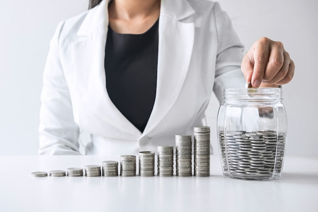 Images of growth stacking coins and business woman hand putting coin into glass bottle (money box) for planning growing business profit step up and savings, future plan and retirement fund concept
