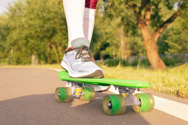 Изображения ноги, стоящей на скейтборде. солнечный вечер в парке. концепция скейтбординга. смешанная техника