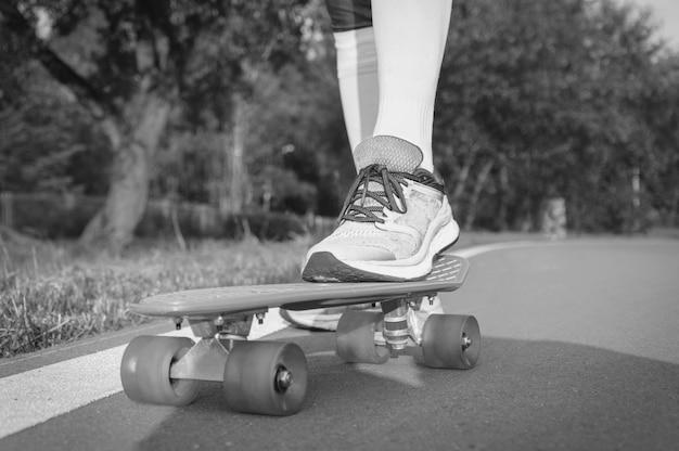 스케이트보드 위에 서 있는 다리의 이미지입니다. 공원에서 화창한 저녁입니다. 스케이트보드 개념입니다. 혼합 매체