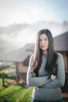 美しい自然のアトラクションに立っている美しいアジアの女性の画像寒い霧の中で長い髪のアジア人女性。