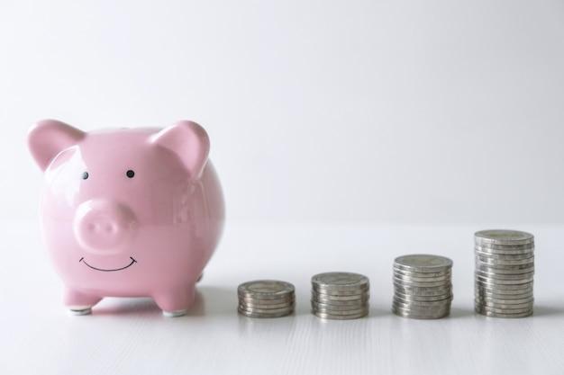 Изображения укладки монет ворс и розовые улыбающиеся копилки для роста и сбережений с копилкой