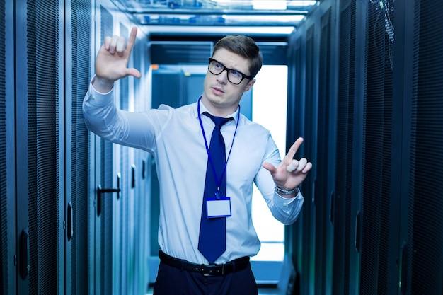 Воображение. сосредоточенный медитативный оператор стоит возле серверных шкафов и воображает