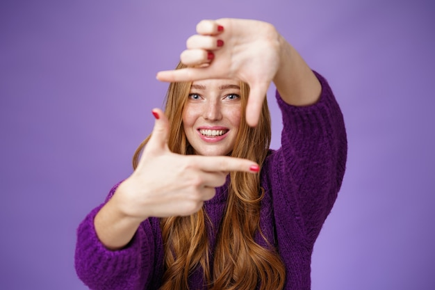Imagine if. portrait of hopeful and carefree creative charming redhead 20s woman showing frame with pulled hands and smiling through it as picturing bright and happy future over purple background.