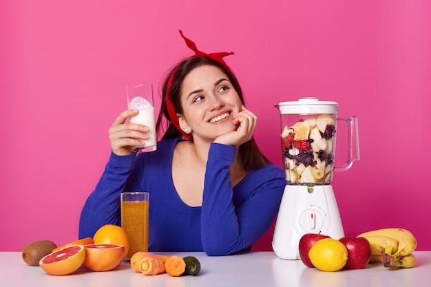 思いやりのある若い女性が青いシャツと赤いヘアバンドを手にミルクのガラスを着て、ピンクのスタジオでポーズをとるスムージーをする準備ができていると想像してください。健康的なライフスタイルとダイエットのコンセプトです。