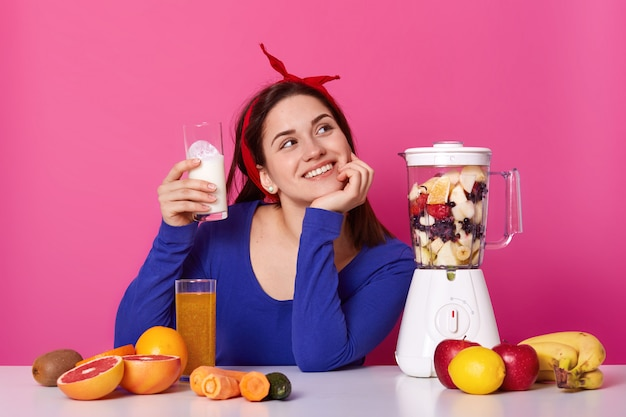 Imagine of young thoughtful woman wears blue shirt and red hair band with glass of milk in her hand, ready to do smoothies, poses on pink studio. healthy lifestyle and diet concept.