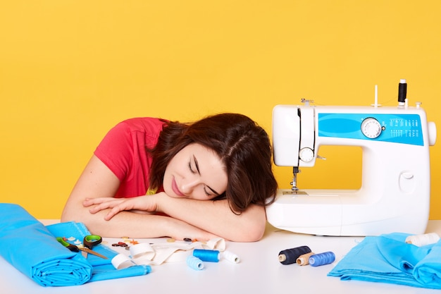 Imagine of young woman works as seamstress