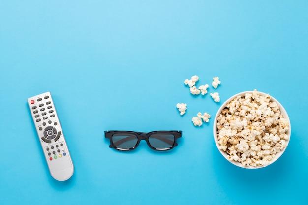 Чаша с попкорном, очки imax, пульт дистанционного управления для телевизора на синем фоне. концепт домашнего кинотеатра, новинки кино, досуг. плоская планировка, вид сверху