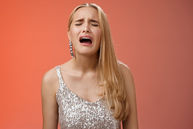 Immature whining spoiled adult rich daughter blond long hair in silver stylish dress complaining sad cruel unfair life crying sobbing frowning sulking upset, standing disappointed red background.