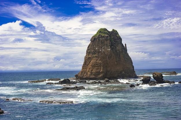 장엄한 구름 풍경 아래 물결 모양의 바닷물에 거대한 암석