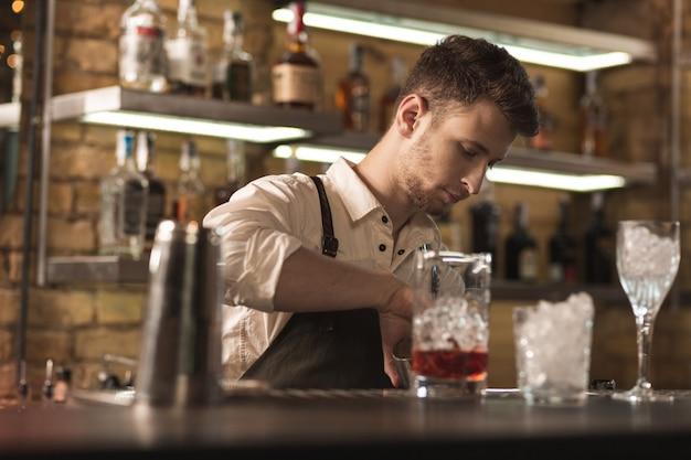 일에 몰두. 바 카운터 뒤에 서서 새로운 음료를 만드는 동안 바텐더로 일하는 잘 생긴 젊은 남자