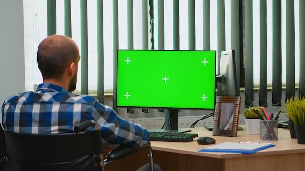 ビデオ会議用のクロマキーを備えたコンピューターを使用して車椅子に固定されたビジネスマン。障害者の障害者フリーランサーが緑色の画面、モックアップ、リモートの同僚と話しているキーでpcを見て