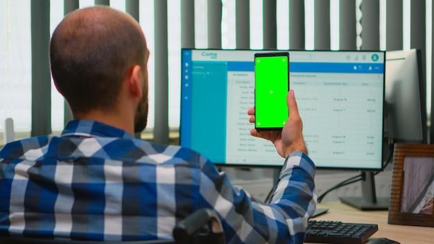 ビデオ会議のためのグリーンスクリーンを備えたスマートフォンを使用して車椅子で固定されたビジネスマン。クロマキーでディスプレイを見ている障害者の障害者フリーランサー、リモートの同僚と話しているモックアップ