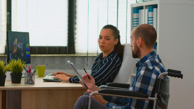 車椅子に座っている不動の起業家が、同僚と話し合っている営業所のクリップボード文書から金融経済統計を説明しています。現代の技術を使用して障害者