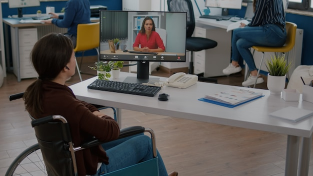 Immobilized entrepreneur talking with coworker during video conference