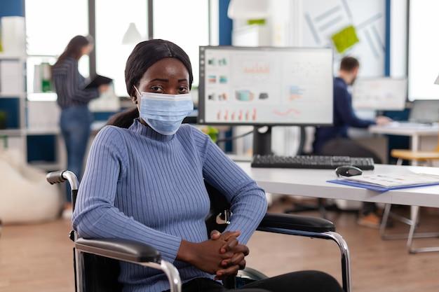 보호 마스크를 쓰고 카메라를보고있는 동원 된 장애인 아프리카 직원 ...