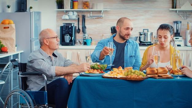 夕食を食べている家族と一緒に祝う動けない年配の男性。グルメな食事の間に話し、笑顔で食事をし、台所のテーブルの周りに座って家で時間を楽しんでいる2人の幸せなカップル。