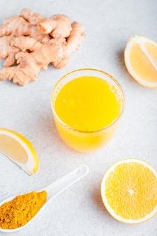柑橘系の果物、生姜、ターメリックを含む免疫増強ドリンク。ニュートラルベージュの背景、静物で秋やウイルスの季節に黄色の紅葉と飲み物やスムージー
