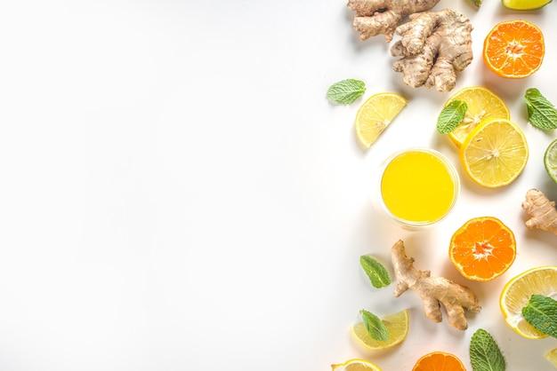 Ингредиенты напитка для повышения иммунитета. домашний сок или коктейль из имбиря и цитрусовых, со свежими цитрусовыми - апельсином, лимоном, лаймом, с корнем имбиря и мятой