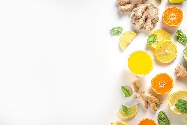 Immunity booster drink ingredients. homemade ginger and citrus juice or cocktail, with fresh citrus fruit - orange, lemon, lime, with ginger root and mint