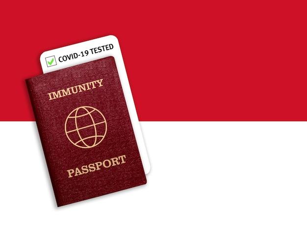 モナコの国旗の上の免疫パスポート。