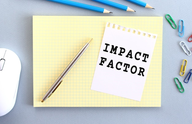 Impact factor is written on a piece of paper that lies on a notebook next to office supplies.